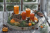 Mediterranean Advent decoration with copper orange candles on trunks