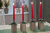 Modern Advent wreath made of candle holders on wooden blocks, red candles