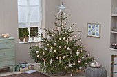 Picea abies decorated with tree balls, stars, white candles