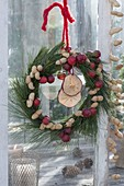 Birdseed wreath made of Pinus (pine) with ornamental apples (Malus)