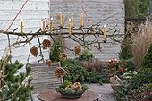 Hanging branch with pine cones and candles over patio table