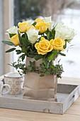 Gelb-weisser Strauss aus Rosa (Rosen) in Papiertüte mit Ranke von Hedera