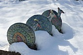 Ceramic peacocks on wooden beams on the snow