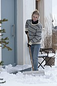 Woman shoveling snow on the terrace