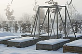Raised beds with trellises in a snow-covered garden