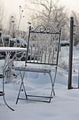 Rauhreif-Kristalle auf nostalgischem Metall-Stuhl