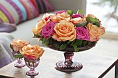 Roses arrangement with moss in shallow footed bowl and glass