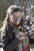 Woman sniffing at blossoming Viburnum bodnantense 'Dawn' branch