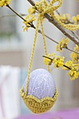 Easter egg in crochet basket on Cornus mas branch