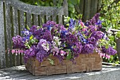 Fragrant spring basket with lilac and perennials
