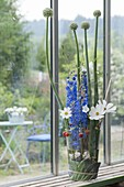 Modern arrangement in glass, delphinium (delphinium), Cosmos
