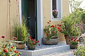 Baskets with zinnias and grasses at the house entrance