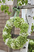 Green and white hydrangea wreath hanged on old wooden ladder