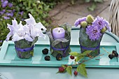Small table decoration with bouquets and lantern on turquoise coaster