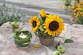 Kleine Deko mit Helianthus (Sonnenblumen), Miscanthus (Chinaschilf)