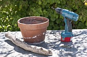 Building flower pot out of clay pot and driftwood
