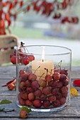 Glass in glass lantern with ornamental apples (malus) and white candle