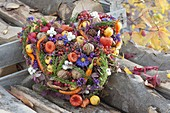 Colorful autumn heart with berries, fruits, nuts, cones, hot peppers