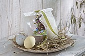 Flat wooden bowl with hay as Easter basket