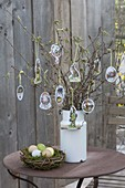 Easter bouquet of branches in old milk can, decorated with Easter wafers