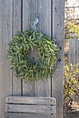 Eucalyptus branches wreath hung on board wall