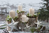 White candles with moss on birch stems