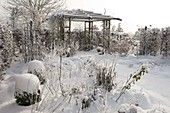 Pavilion in the snowy garden, flowerbeds with perennials