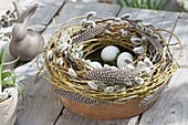 Clay bowl with wreath of Salix (willow, kitten willow) and feathers
