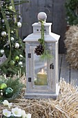 Wooden lantern with green candle on straw bales