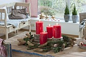 Simple Advent decoration with red candles on wooden discs