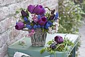 Small bouquet in wicker vase, Tulipa 'Purple Prince', Viburnum