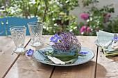 Glass bowl with Allium (garlic) flower and geranium