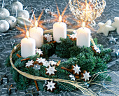 Advent wreath made of branches, cinnamon stars and white candles