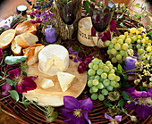 Style with cheese, baguette, grapes, clematis flowers