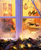 Winterliches Fenster mit Blick ins adventlich dekoriertes Wohnzimmer