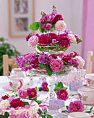 Table decoration with etagere made of glass bowls filled with rose petals
