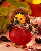 Pumpkin figure, ornamental gourds, rose hips, sisal