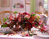 Autumn arrangement with roses, rose hips, Erica and berry jewelery