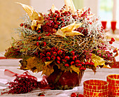 Autumn bouquet with ornamental corn, autumn leaves and berry decorations