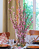 Prunus persica, peach blossoms in glass vase, glass balls as decoration