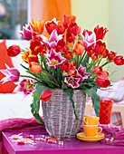 Tulipa (tulip), Vaccinium (blueberry) branches in basket vase