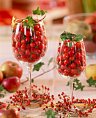 Rose rosehips in wine glasses and as a wreath, hedera ivy, malus apples