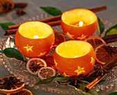 Citrus oranges hollowed out as tealight holders, slices of orange, leaves, star