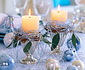 Silver ice cream cup with candle, tinsel and balls