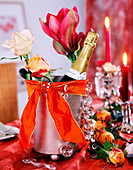 Rose, hippeastrum (amaryllis) in champagne cooler, orange ribbon, glass