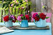 Small bouquets in jugs on wooden board