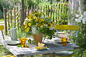 Yellow summer bouquet on table in the garden