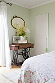 Old sewing machine table in a vintage bedroom with pale green walls