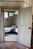 View into bedroom with twin beds through open panelled door