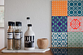 Spices and oil bottle next to patterned tiles